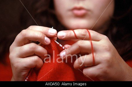 Woman Knitting With Red Wool In Devon In England