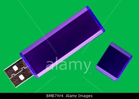 Purple flash drive with cap on green background stock photo by John Rocha
