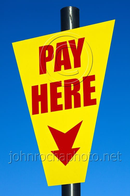 Bright Yellow and Red Pay Here Sign in a Public Car Park
