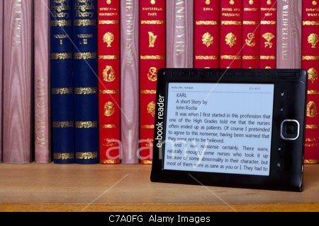 A black e book reader on a shelf with classical books.