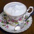 cappuccino in a bone china cup with a silver spoon